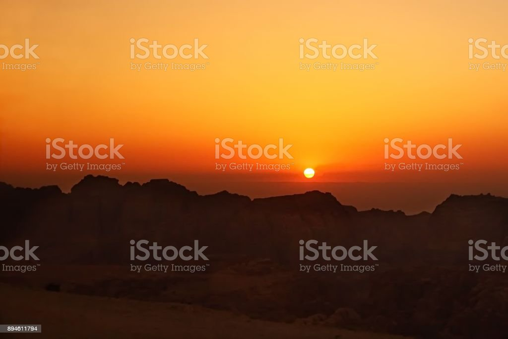 sunset with red sun and mountain shapes stock photo