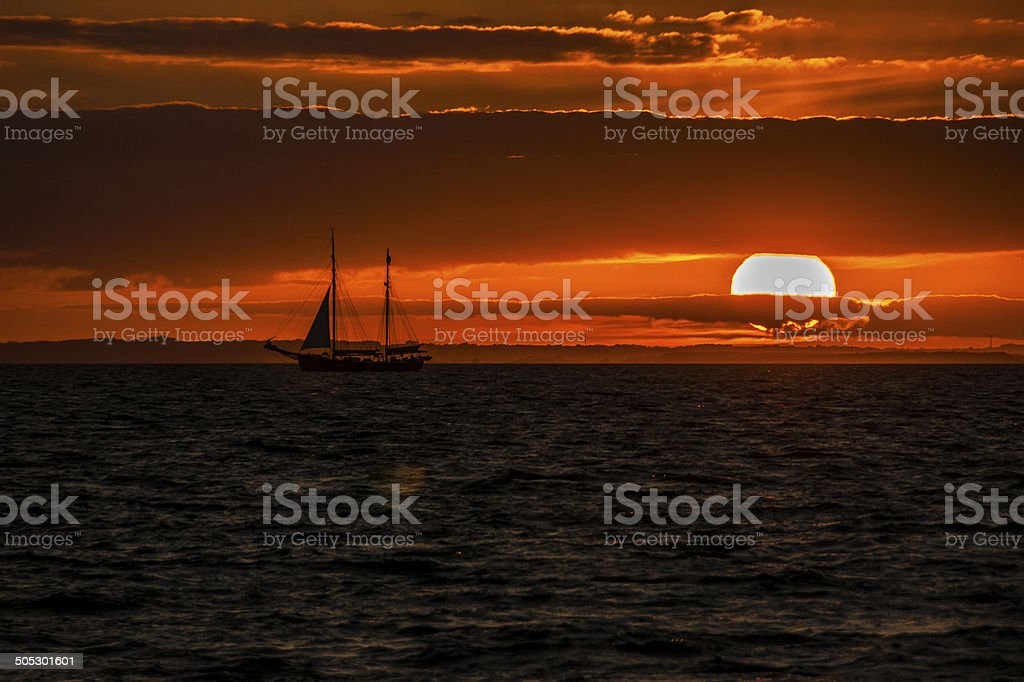 Sunset with sailing boat stock photo
