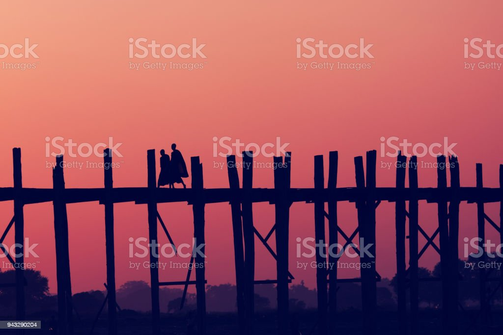Sunset with silhouettes of monks on Bridge U-Bein teak bridge is the longest. stock photo