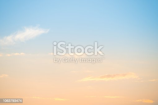 Sunset with sun and clouds on blue and orange pastel sky