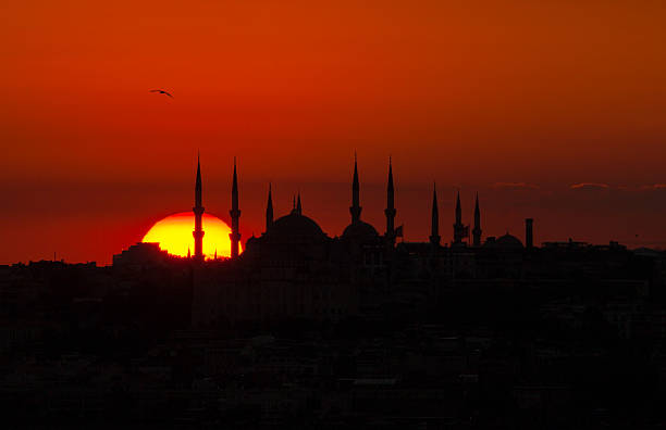 Sunset with sun behind silhouette in Istanbul,Turkey Silhouette of blue mosque in historical area of istanbul and bosphorus with dramatical cloudy sunset religious celebration stock pictures, royalty-free photos & images