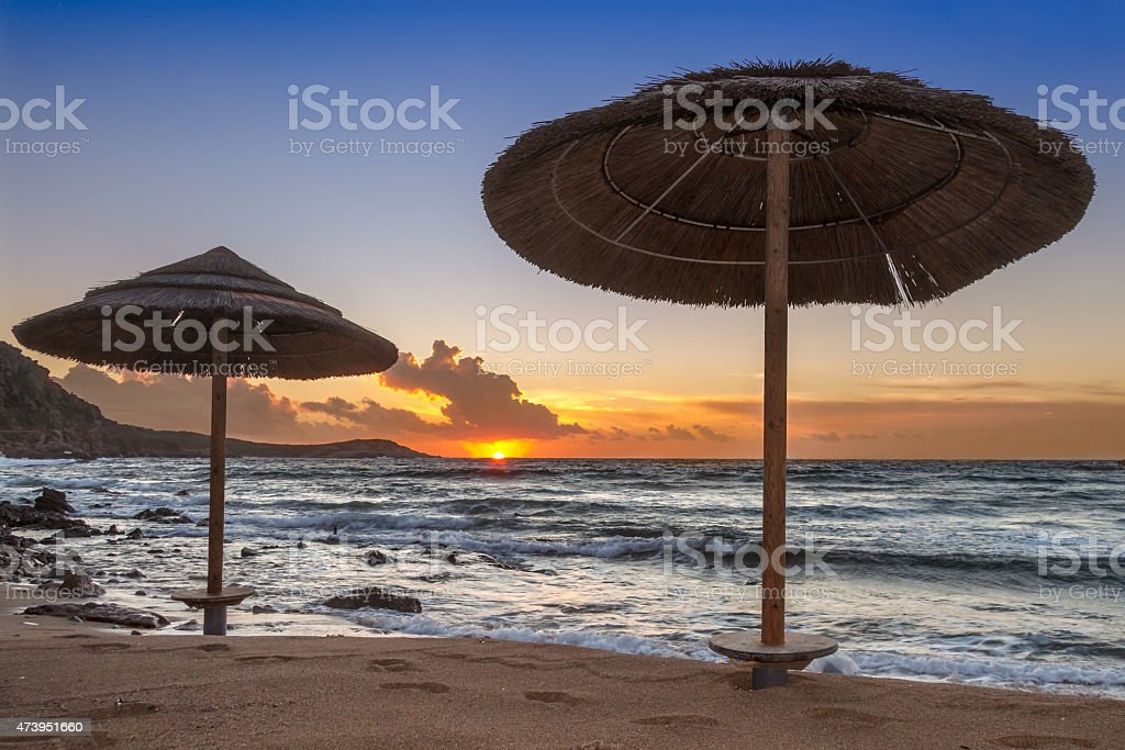Sunset with two umbrellas stock photo