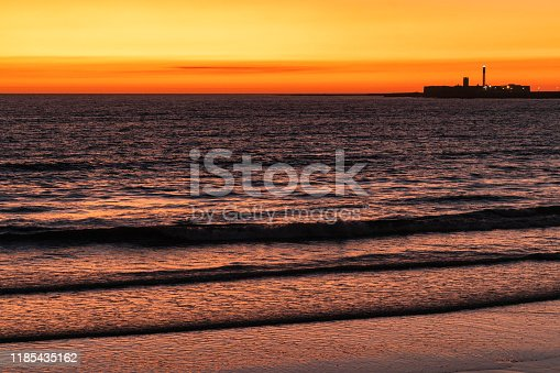 1130689824 istock photo Sunset with view at the Lighthouse in Cadiz, Andalusia, Spain 1185435162