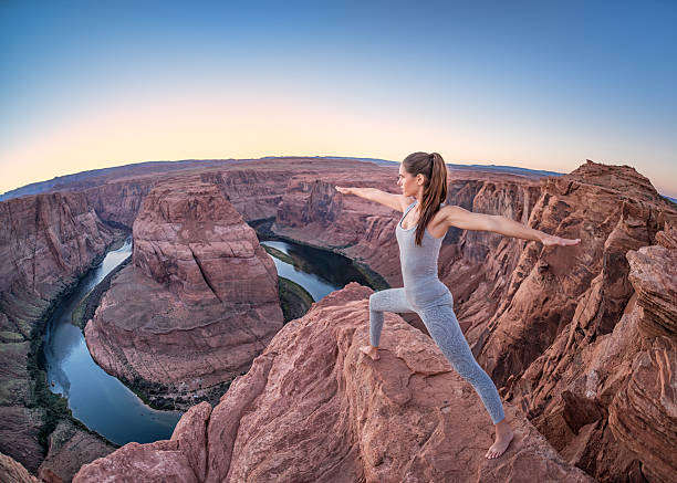 Sunset Yoga, Feeling Nature - Horseshoe Bend Beautiful woman in a Yoga Pose standing right on the edge 1000 feet above the Colorado River of the Horseshoe Bend. Extreme Wide Angle shot. Nikon D810. horseshoe bend colorado river stock pictures, royalty-free photos & images