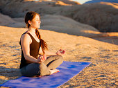 A young woman doing yoga at sunset on the red rocks of Moab, Utah USA.