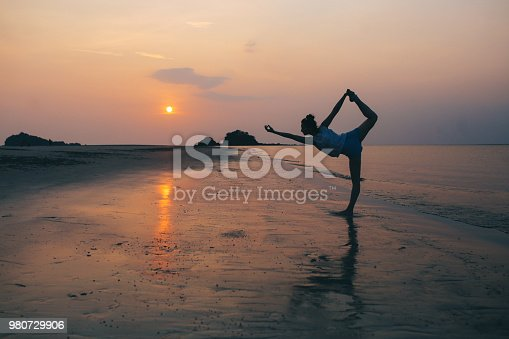Vintage toned image of a deserteded beach in Koh Lanta, Thailand. A silhouette of a young woman can be seen, doing yoga or just some stretching exercise after a nice day of swimming and enjoying the seaside.