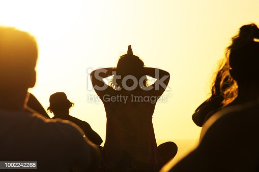 Silhouette of a woman instructing yoga class outdoors at sunset