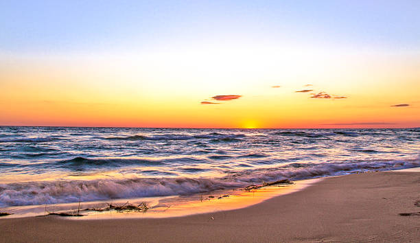 sunsets over a wide sandy beach in paradise - meeroever stockfoto's en -beelden