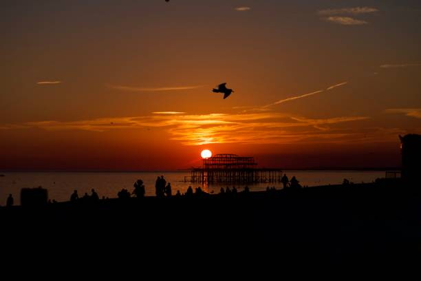 Sunsetting behind the West Pier, Brighton Silhouette view of the busy Brighton Beach with the sun dropping behind the ruined West Pier off the shore in Brighton, England. skeable stock pictures, royalty-free photos & images