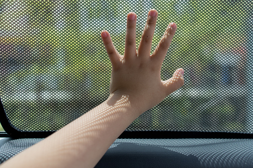 Close up kid hand touching fabric made sunshade in the car side window