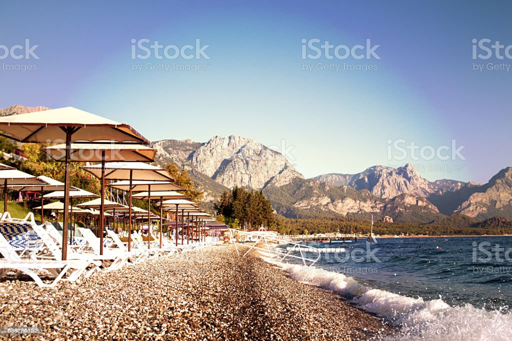 Sunshades and chaise lounges on beach. Summer seascape. stock photo