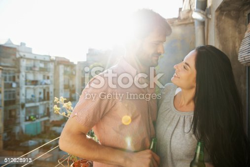 Shot of a loving young couple standing together outside on a balcony with beers in their hands