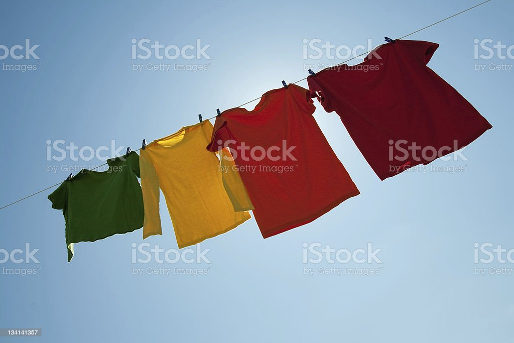 Sunshine behind colorful clothes on a laundry line royalty-free stock photo
