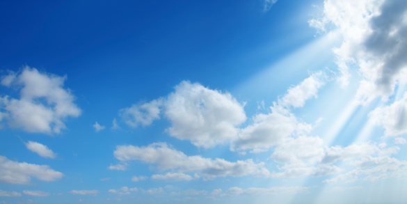 partly  cloudy and sunny blue sky with sunbeam.