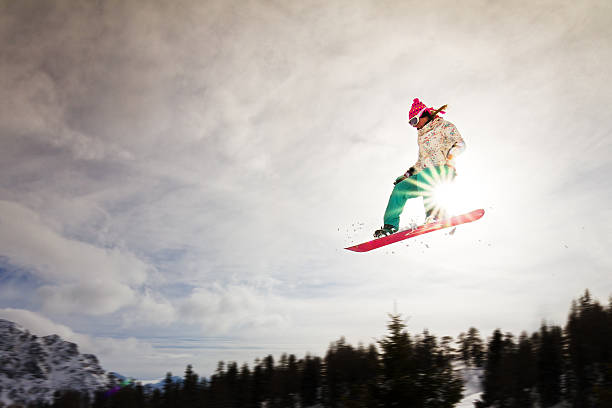 Sunshine jump Female snowboarder making an awesome big jump of a kicker bruneck stock pictures, royalty-free photos & images