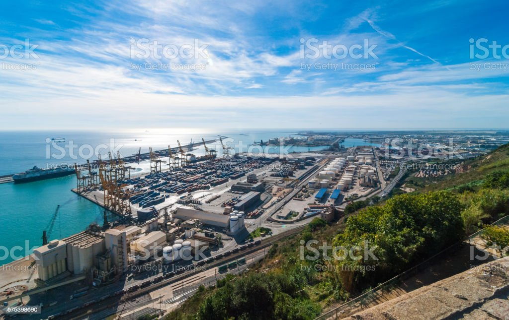 Sunshine on Balearic sea & Barcelona industrial shipping and rail ports on a blue-sky day. royalty-free stock photo