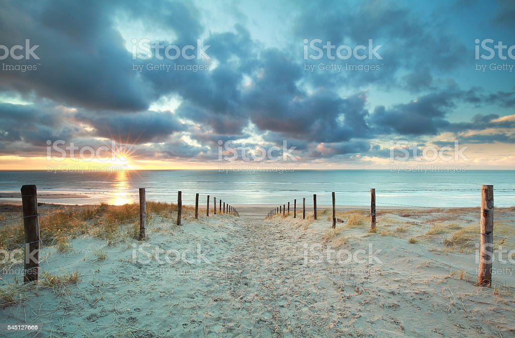 sunshine on sand path to sea beach stock photo