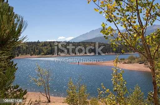 Sunshine sparkles on the water a fisheman stands on a point and aspen leaves turning yellow shimmer at Chrystal Reservoir half way up Pikes Peak mountain near Colorado Springs