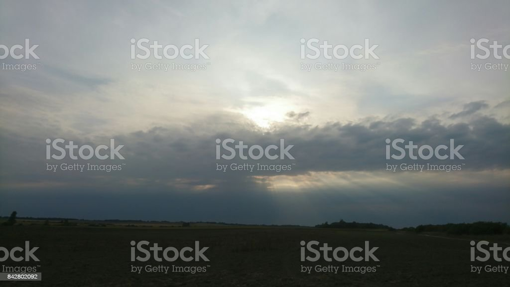 Sunshines from cloudy sky at night in Lithuania stock photo