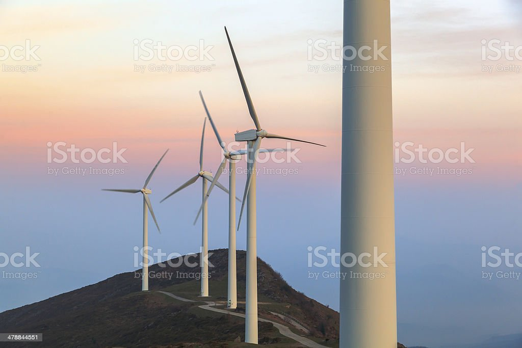 sunsset and wind turbine stock photo