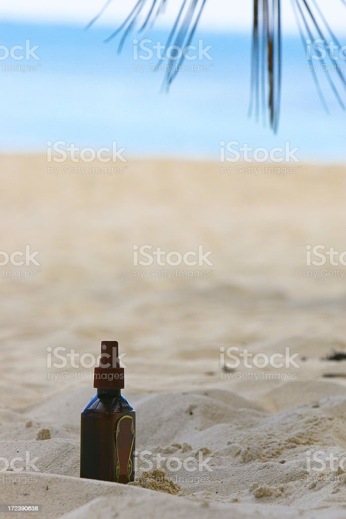 Suntan lotion bottle buried in sand royalty-free stock photo
