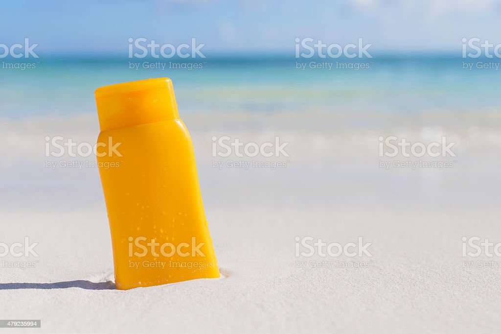 Suntan lotion bottle on the beach stock photo