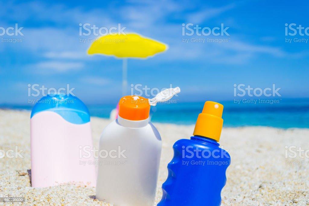 suntan lotion bottles on the sand stock photo