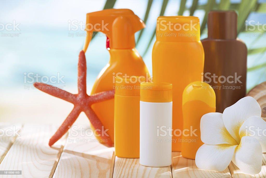 Suntan lotion bottles, sea shell,star and plumeria flower royalty-free stock photo