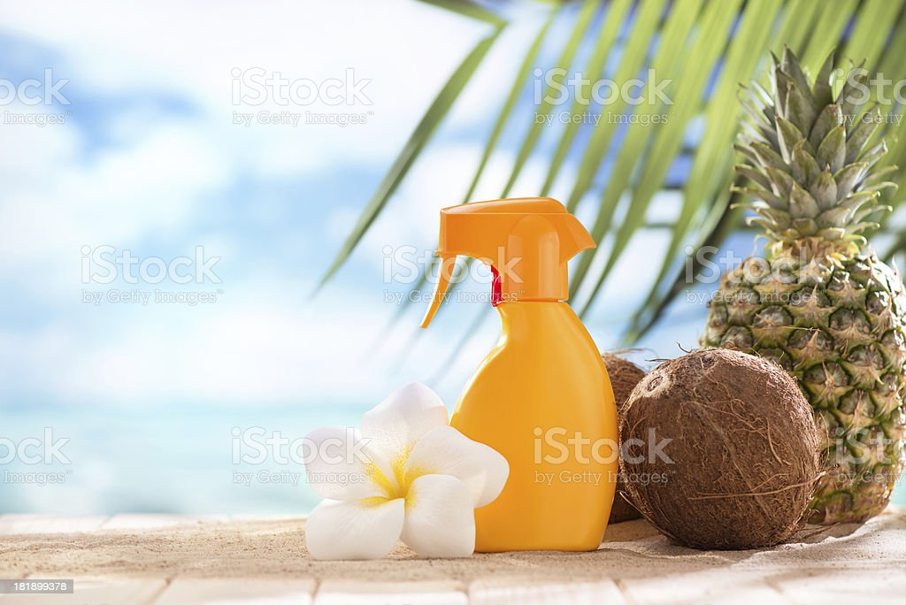 Suntan lotion, coconuts and plumeria flower with copy space royalty-free stock photo
