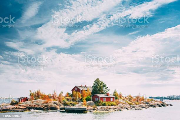 Photo of Suomi Or Finland. Beautiful Red Finnish Wooden Log Cabin House On Rocky Island Coast In Summer Sunny Evening. Lake Or River Landscape. Tiny Rocky Island Near Helsinki, Finland