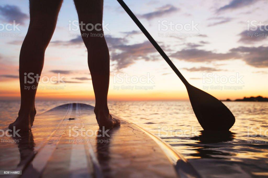 SUP, standup Paddle am Strand bei Sonnenuntergang – Foto
