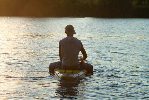 Sup surfer sits on the sup board in the golden light
