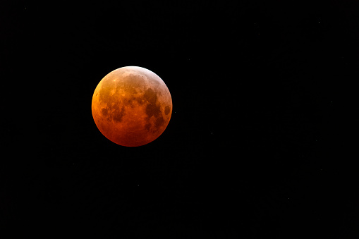 The super blood wolf moon lunar eclipse of January 2019 in the dark night sky.