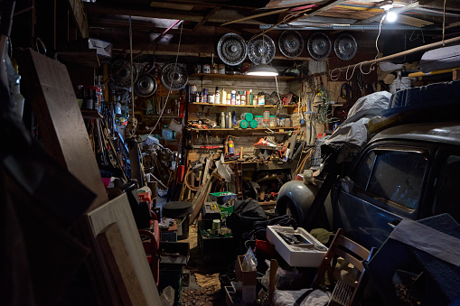 An old garage in a barn with heels of containers and metal and scrap alongside a vintage old car.