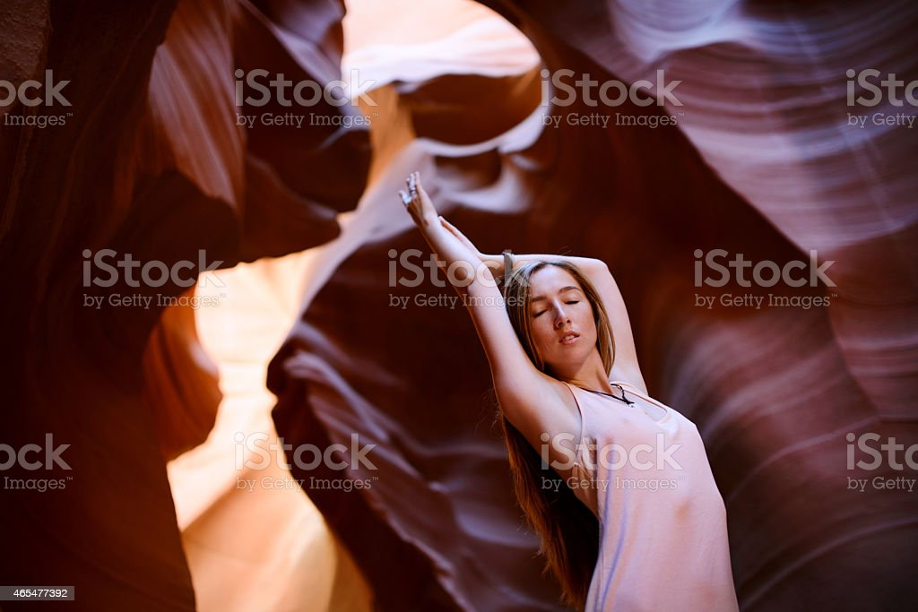Super cute girl surrounded by red cliffs of Antelope Canyon stock photo
