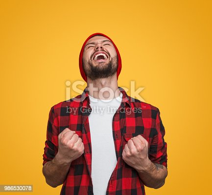 istock Super excited hipster guy celebrating win 986530078