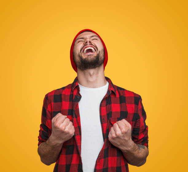 Super excited hipster guy celebrating win Trendy bearded man in checkered shirt and hat holding fists and screaming with euphoria celebrating success on orange background lottery stock pictures, royalty-free photos & images