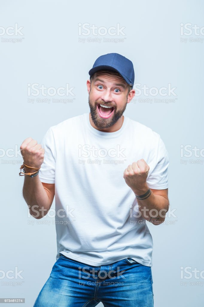 Super excited man Portrait of excited young man with his clenched fist in white background Adult Stock Photo