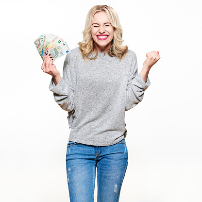 Super excited young woman in grey sweater and jeans holding bunch of Euro banknotes, clinching fists, celebrating winning lottery. Ecstatic woman holding lots of money, isolated on white background.