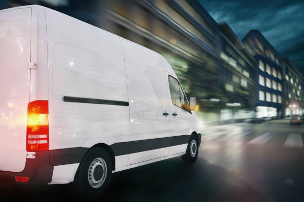 Super fast delivery of package service with a fast moving van on cityscape stock photo