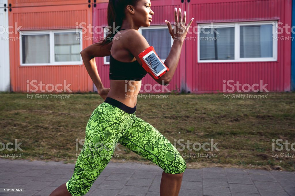 Super fit woman exercising in city industrial district -...