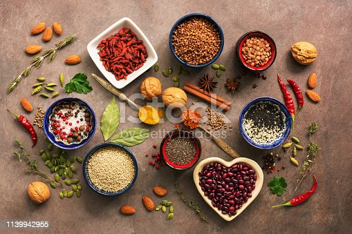 istock Super food background, a variety of cereals, legumes, spices, herbs, nuts. Various seasonings for cooking on brown background. Top view, overhead. 1139942955
