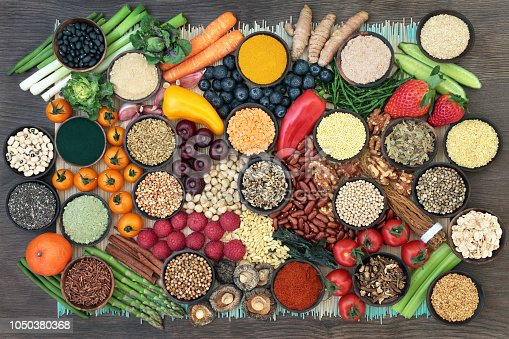 Liver detox super food with fruit, vegetables, herbs, spices,legumes, nuts, seeds, grains, cereals and herbal medicine. Health foods high in antioxidants, vitamins  & fibre.  Top view on bamboo and oak.