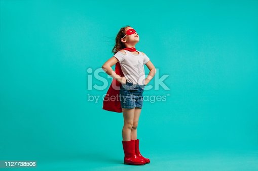 Girl wearing red gumboots, cape and eye mask standing with her hands on hips in studio. Super girl looking away on blue background.