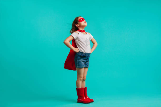 Super girl looking away Girl wearing red gumboots, cape and eye mask standing with her hands on hips in studio. Super girl looking away on blue background. girl power stock pictures, royalty-free photos & images