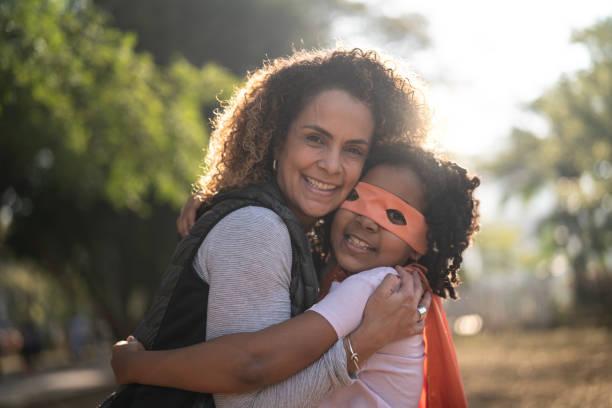 super hero dotter omfamnar hennes mor - superwoman barn bildbanksfoton och bilder