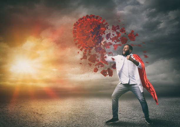 Super hero doctor with red cloak wins against viruses stock photo