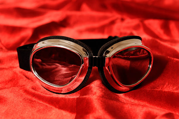 Super Hero Goggles Sitting On Red Satin Cape Blank and Silver Goggles Sitting On Super Heroe's Red Satin Cape. Close Up. Lots of copy space. Material has grainy effect in it. alias stock pictures, royalty-free photos & images