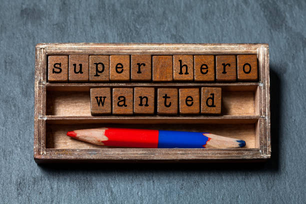 Super hero wanted phrase. Recruiting and personal searching concept quote. Vintage box, wooden cubes with old style letters, red blue pencil. Gray textured background. Close-up, up view, soft focus – Foto
