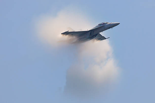 f-18 super hornet travels subsonic speed with visible vapor cone - sonic boom stock photos and pictures